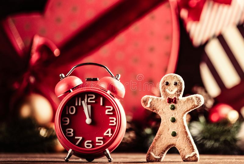 Gingerbread man and alarm clock. Photo of the alarm clock and gingerbread man on the christmas decorations background royalty free stock photos
