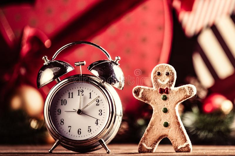 Gingerbread man and alarm clock. Photo of the alarm clock and gingerbread man on the christmas decorations background royalty free stock photography