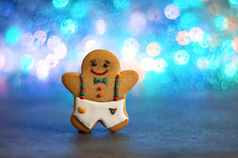 Gingerbread man on the background of multi-colored bokeh lights. Very soft, selective focus. Christmas baking. Copy of space stock images