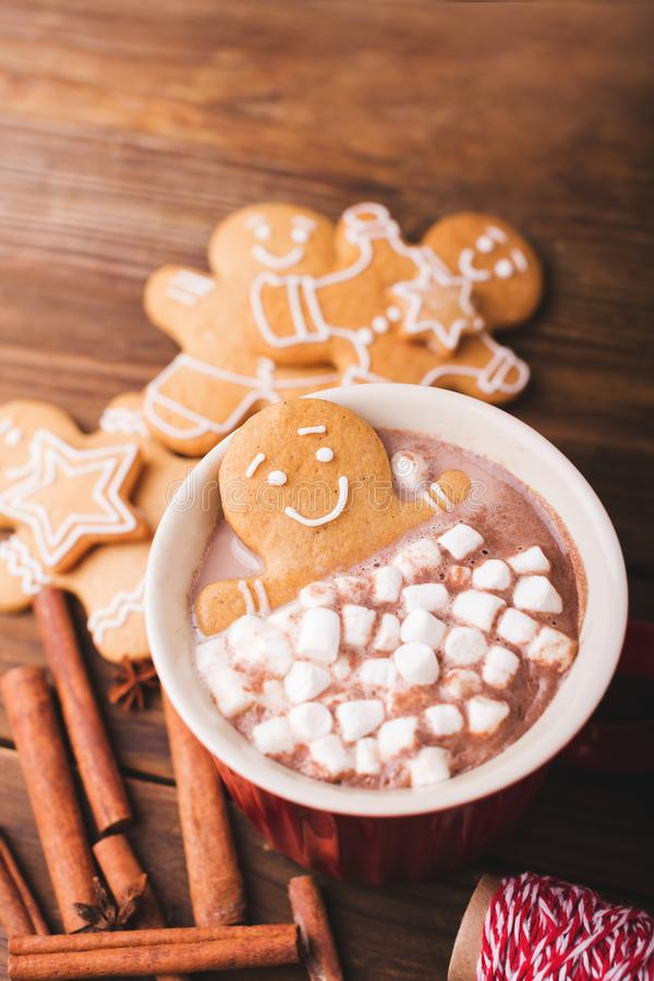 Gingerbread man bathes in a cup of chocolate or cocoa with marshmallow. Gingerbread Man in red cup. Gingerbread man bathes in a cup of hot chocolate or cocoa stock photography