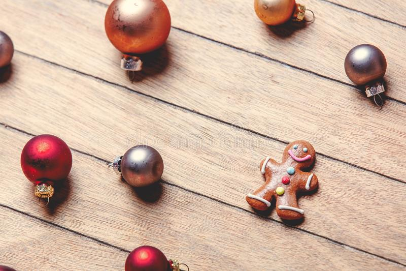 Gingerbread man with Christmas baubles around. On wooden table. Above view in old color style stock photos