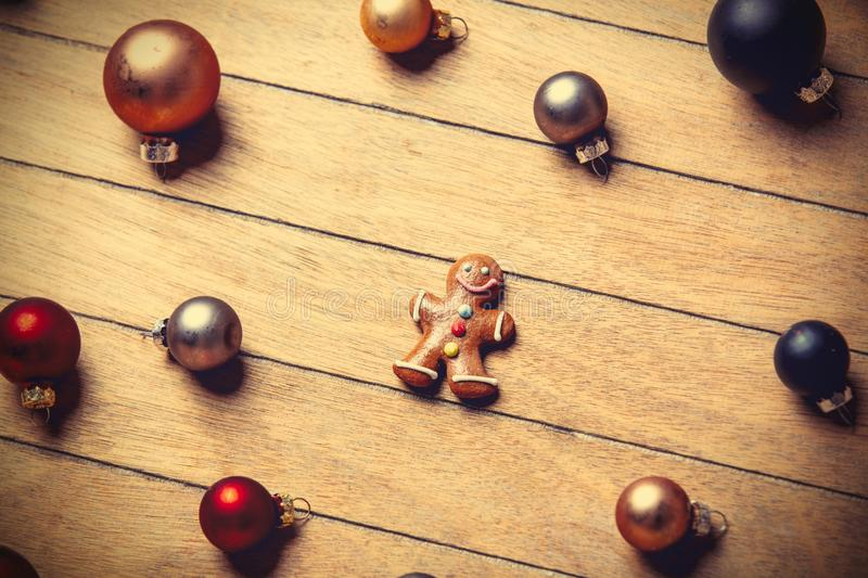 Gingerbread man with Christmas baubles around. On wooden table. Above view in old color style royalty free stock photo