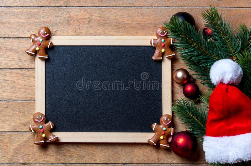 Gingerbread man with Christmas decoration. And blackboard on wooden table. Above view in old color style stock photo