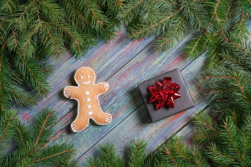 A gingerbread man with Christmas decorations and lots of fir bra. Nches. Christmas gift box. Holiday greeting card. Copy spase, spase for text royalty free stock photos