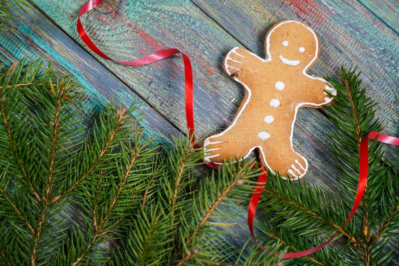 A gingerbread man with Christmas decorations and lots of fir branches. Christmas gift box. Holiday greeting card. Copy spase, spase for text royalty free stock images