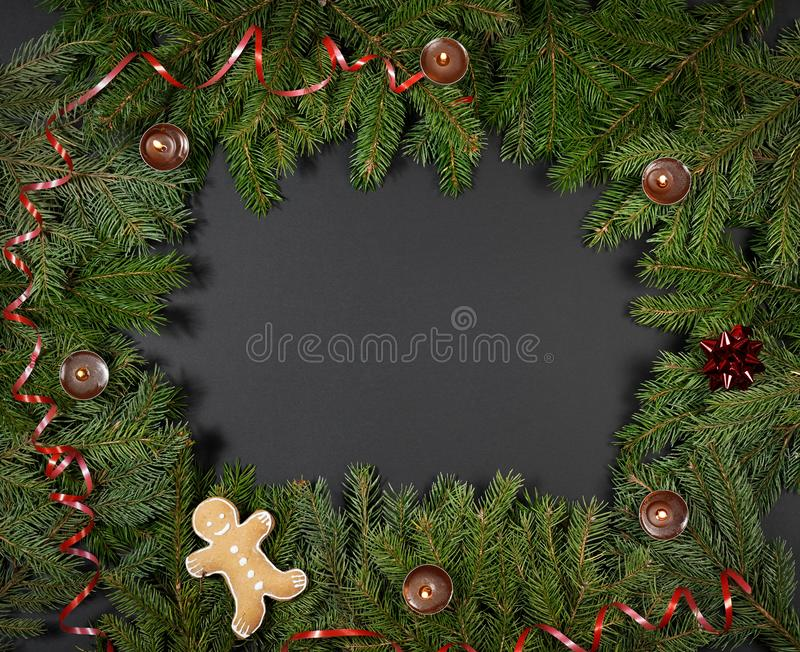 A gingerbread man with Christmas decorations and lots of fir branches royalty free stock image