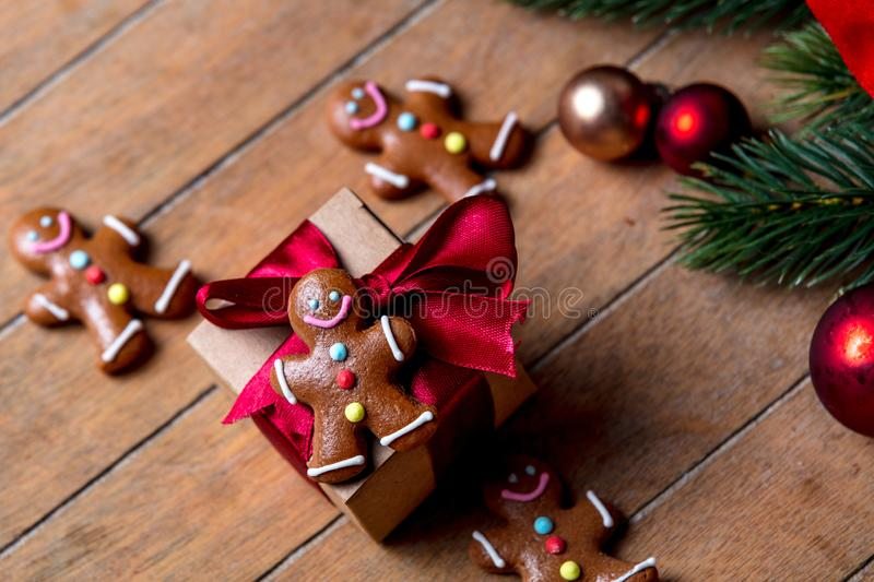 Gingerbread man with Christmas gift box. On wooden table. Above view in old color style stock photography