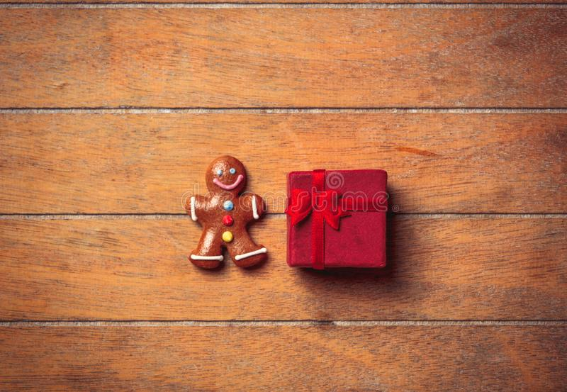 Gingerbread man with Christmas gift. On wooden table. Above view in old color style royalty free stock photos