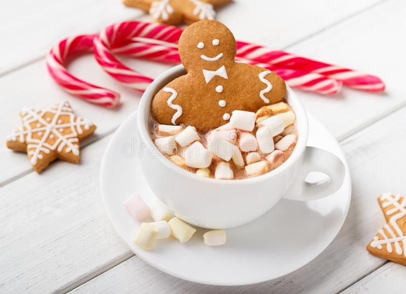 Gingerbread man in Christmas hot chocolate cup. And candy canes on white background royalty free stock image