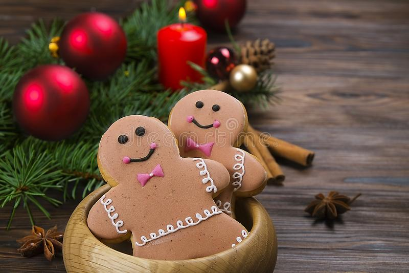 Christmas and New Year Gingerbread man Cookie on wooden table close up. Gingerbread man cookie with festive decoration on brown wooden table royalty free stock images