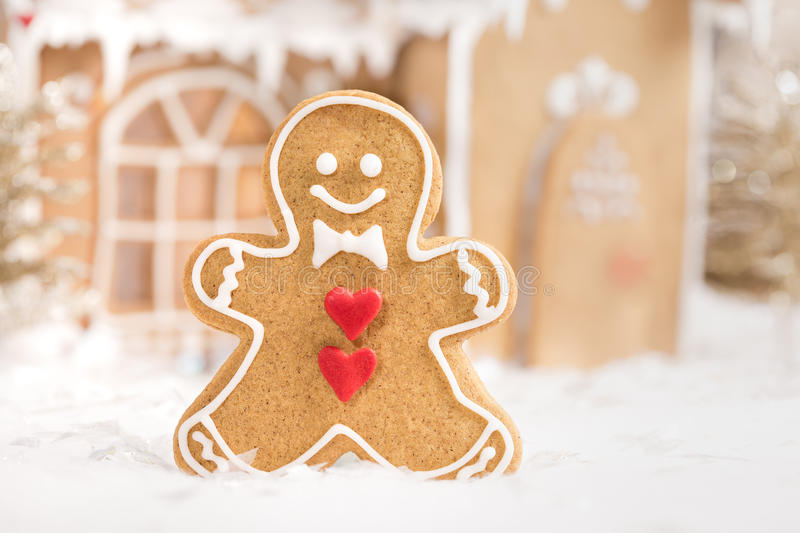 Gingerbread Man. Cookie standing in front of a gingerbread house stock images