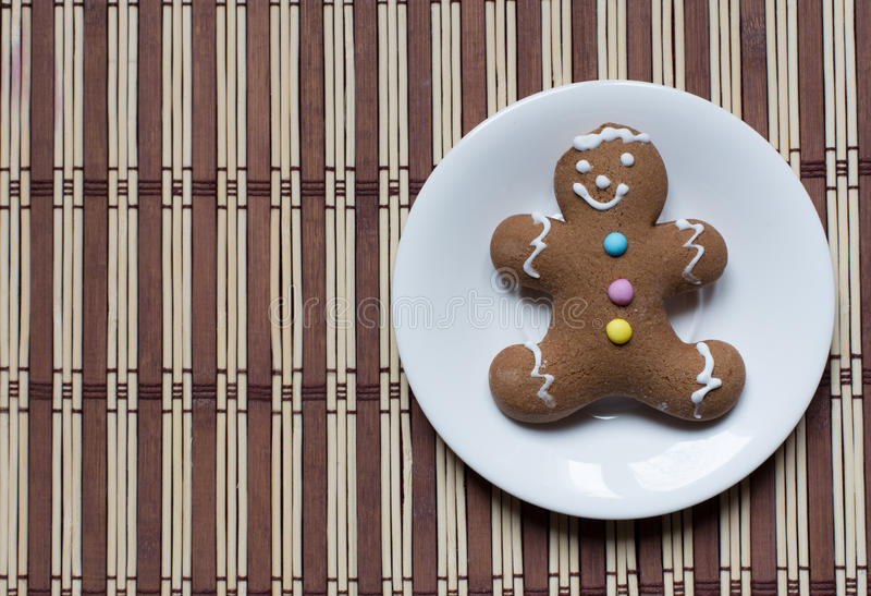 Gingerbread man cookie. On whit plate on striped background royalty free stock photography