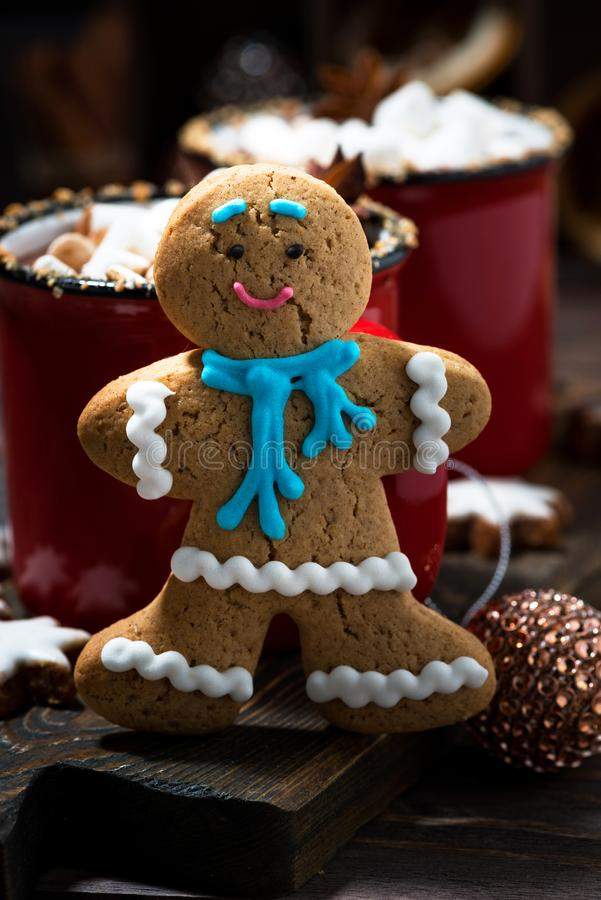 Gingerbread man cookies and hot chocolate, vertical closeup. Gingerbread man cookies and hot chocolate, closeup royalty free stock photography
