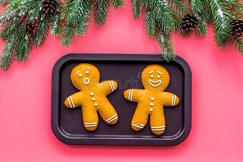 Gingerbread man cookies for New Year meal near spruce branch on white background top view.  stock photos