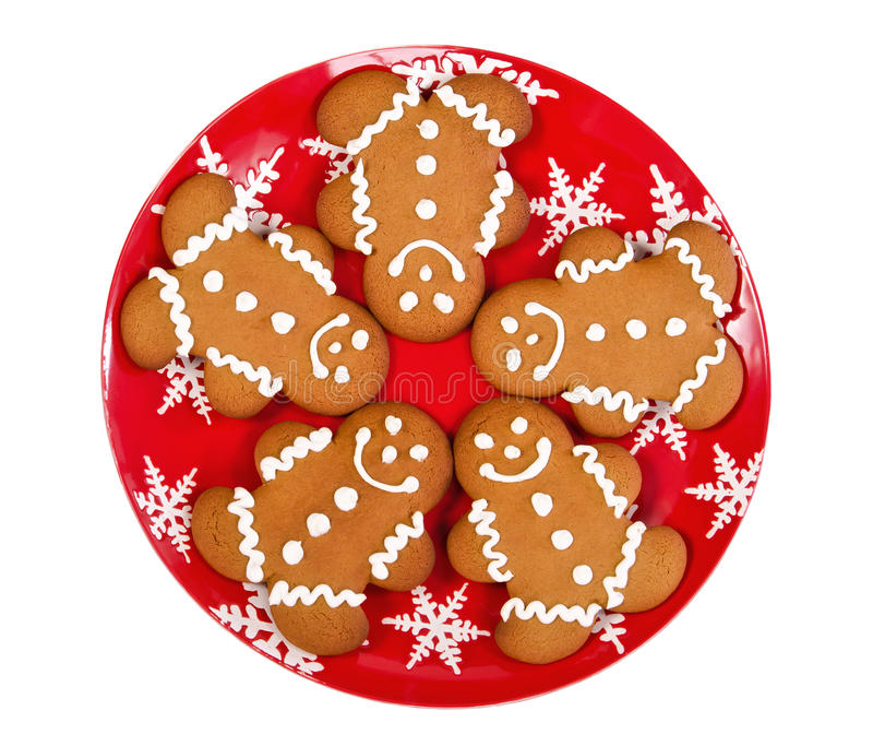 Gingerbread man cookies. On red Christmas plate, isolated over white royalty free stock photo