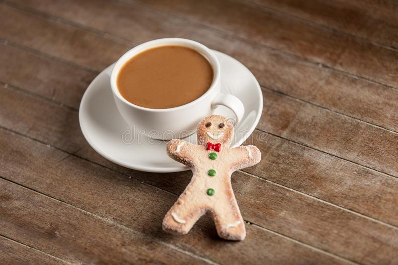 Gingerbread man and cup of coffee. On wooden table royalty free stock images