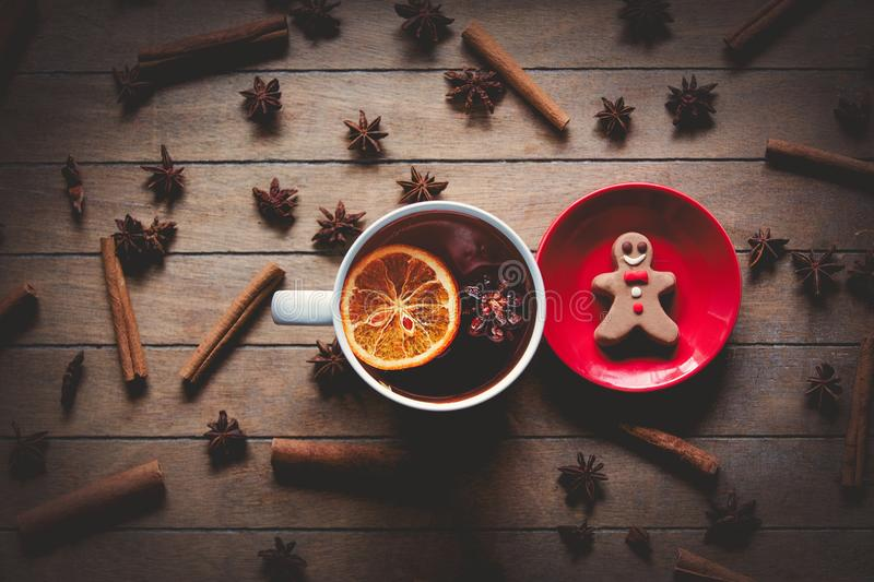 Gingerbread man and cup of tea. With cinnamon and star anise around on wooden background stock images