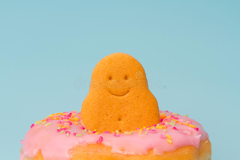 Gingerbread Man In A Donut. A happy gingerbread man sitting in a pink iced donut on a blue background stock image