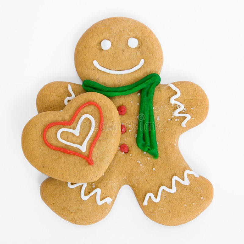 Gingerbread man with gingerbread heart. Smiling gingerbread man holds iced gingerbread heart stock photography