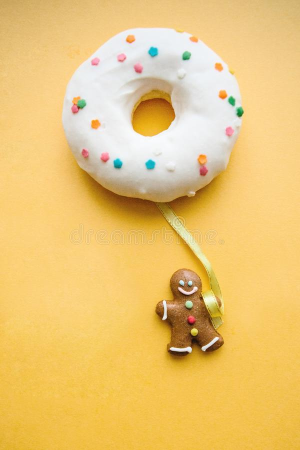 Gingerbread man holds a donut in his hand that looks like a balloon. Creative idea. Holiday concept.  royalty free stock images