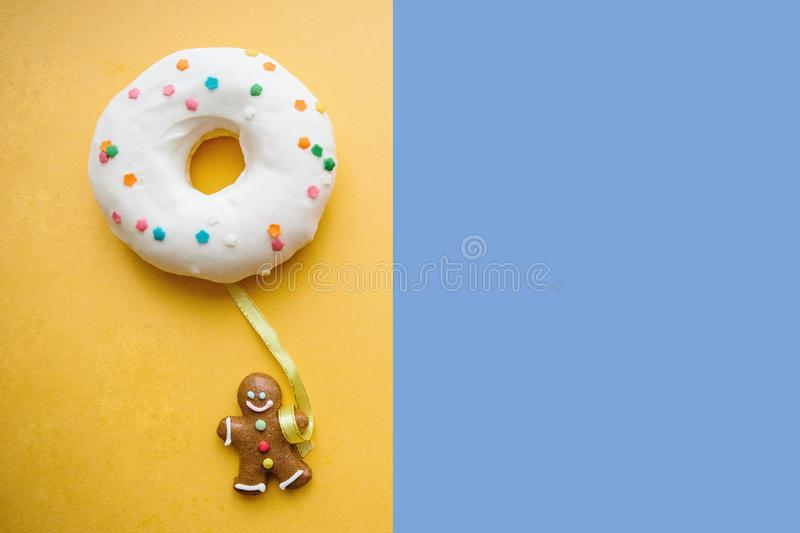 Gingerbread man holds a donut in his hand that looks like a balloon. Creative idea. Holiday concept. Nearby place for. Text royalty free stock photo