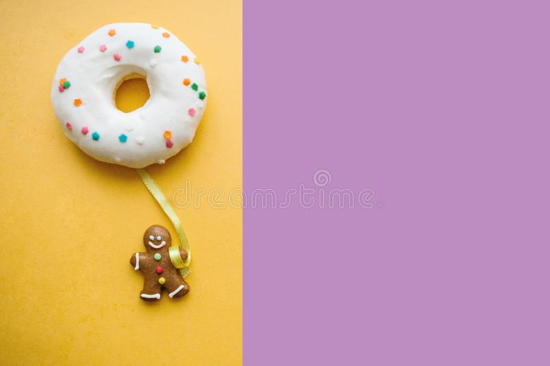 Gingerbread man holds a donut in his hand that looks like a balloon. Creative idea. Holiday concept. Nearby place for. Text royalty free stock images