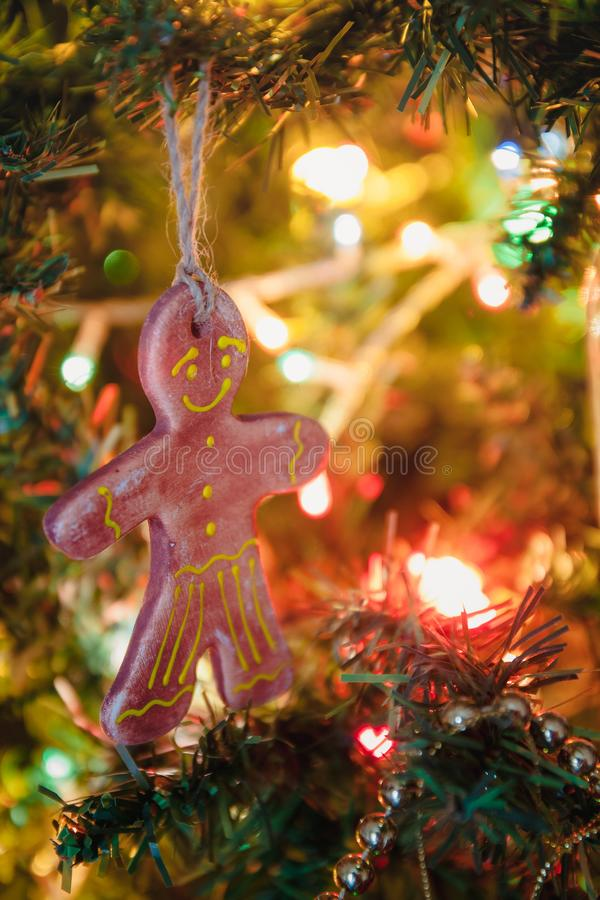 Gingerbread man on a holiday tree, Christmas toy, life style, garland with lights.  royalty free stock photos