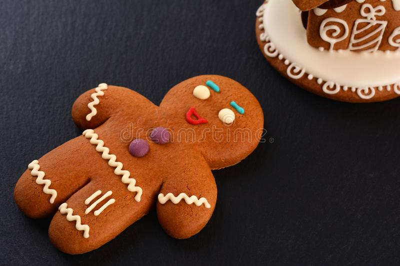 Gingerbread Man and Gingerbread house on dark background. Christmas or New Year composition. Christmas card royalty free stock image