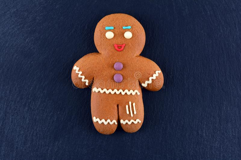 Gingerbread Man lying on dark background. Christmas or New Year composition. Christmas card stock photo