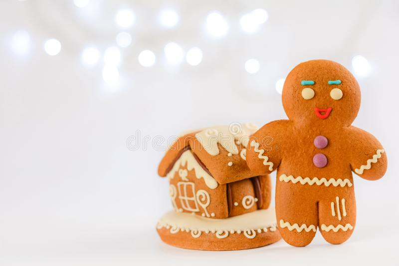 Gingerbread man near the house on the background of beautiful bokeh snowflakes. Christmas food decorations. stock photography