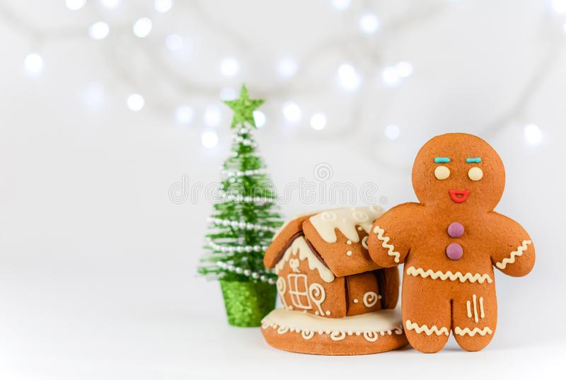 Gingerbread man near the house on the background of beautiful bokeh snowflakes. Christmas food decorations. royalty free stock photo