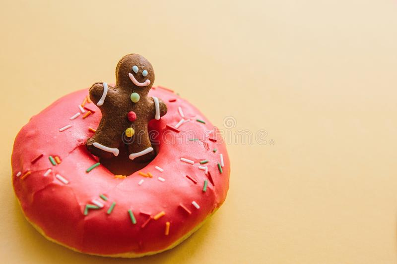 Gingerbread man resting in a donut. Creative idea. Celebratory concept.  royalty free stock image