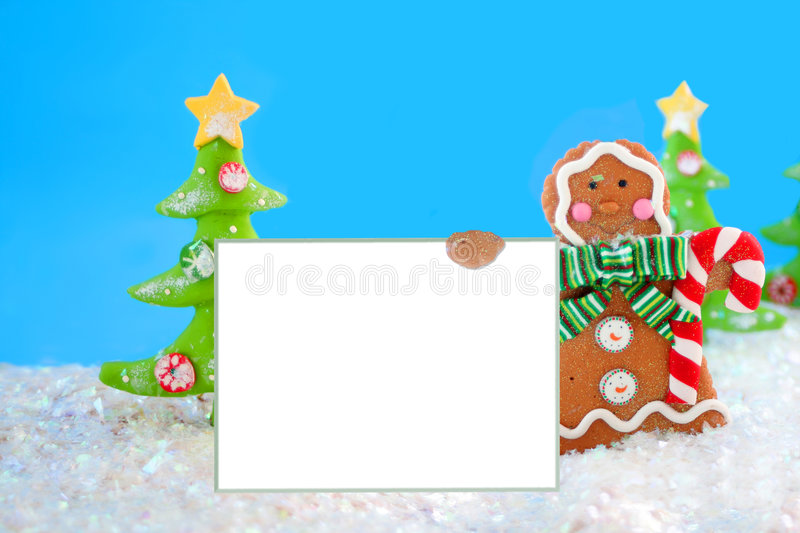 Gingerbread man sign. Gingerbread man cookie in a winter wonderland holding a blank sign with christmas tree in the background stock image