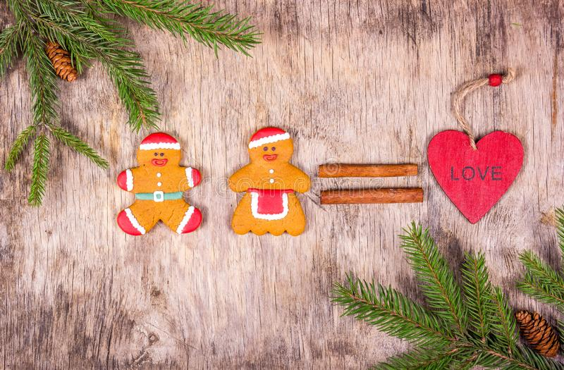 Gingerbread man and gingerbread woman. Christmas background with fir tree and homemade cookies. Love gingerbread men. Copy space royalty free stock photo