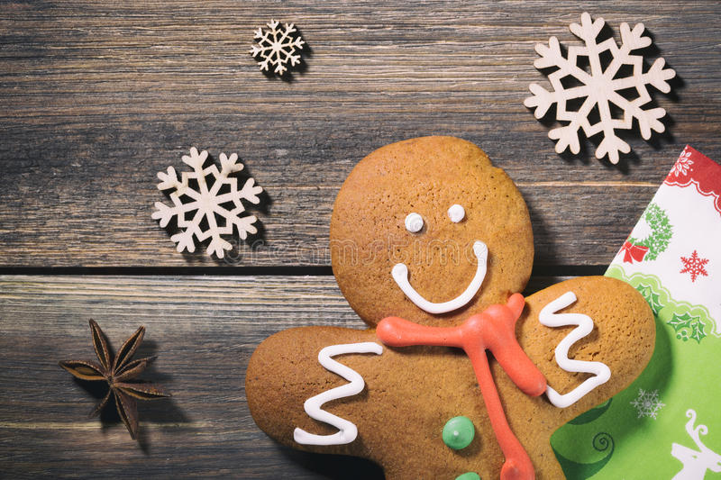 Gingerbread Man on Wood. Christmas Holiday Background with Gingerbread Cookie, decorative snowflakes, napkin and spice.  royalty free stock photo