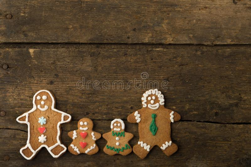 Gingerbread men family on wood. Gingerbread men family on a rustic wooden table stock photography
