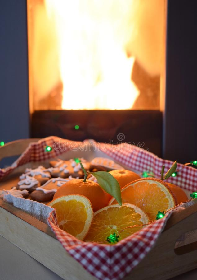 Gingerbread and oranges on a tray in front of the chimney royalty free stock photos