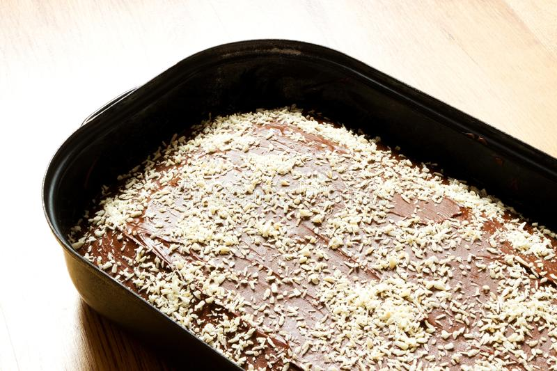 Gingerbread in the pan. Cake with brown icing and coconut sprinkles, baked gingerbread in black baking pan stock photos