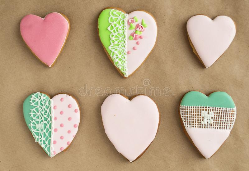 Gingerbread gingerbread in pink glaze, on craft background. Bakery products. Gingerbread in the shape of a heart stock photo