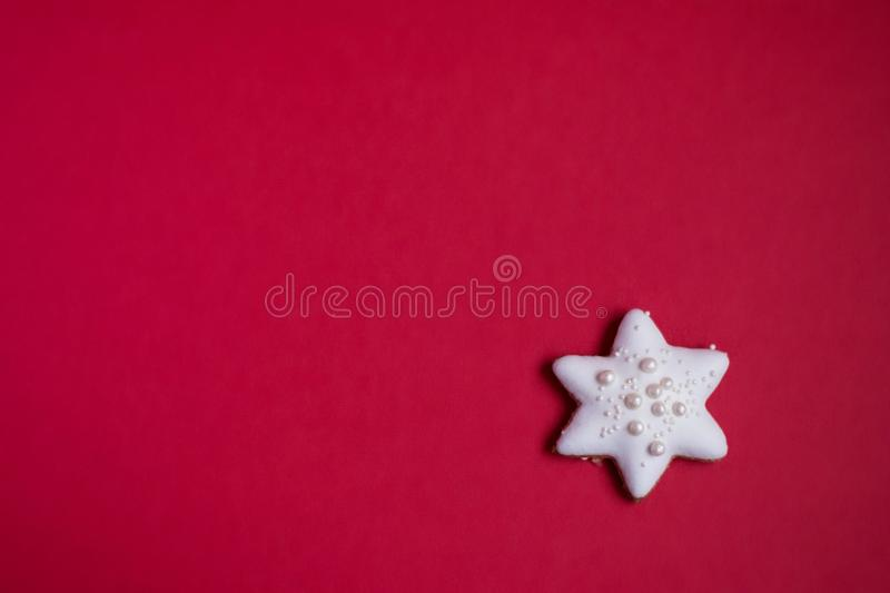 Gingerbread star with white icing and sprinkles on red background stock photos
