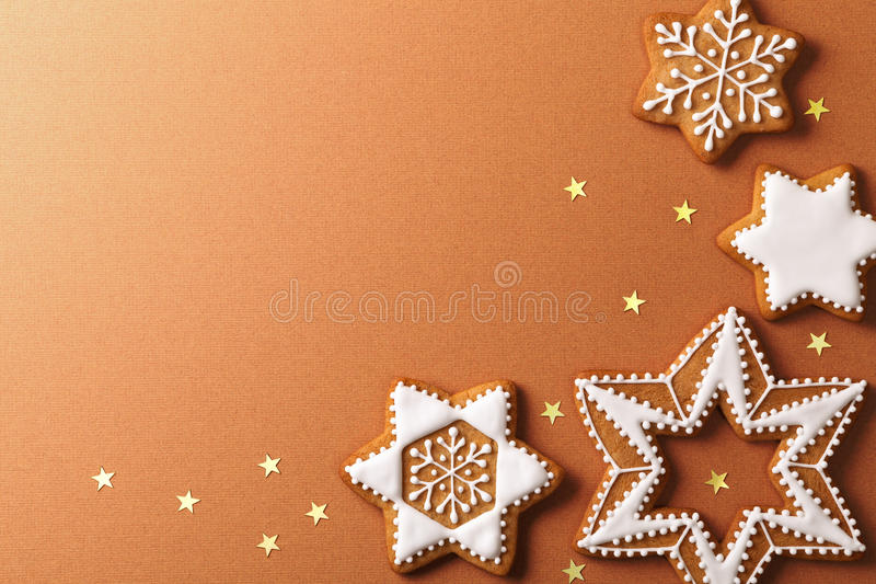 Gingerbread stars. Christmas gingerbreads with golden stars on brown paper background. Top view stock photo