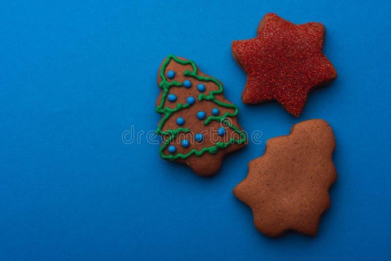 GingerbreadDelicious圣诞节的姜饼曲奇饼在蓝色背景 库存照片
