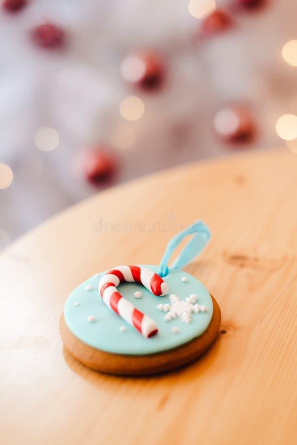 Gingerkaka på bordet nära den vita julgranen med gyllene bokeh-ljus royaltyfri fotografi