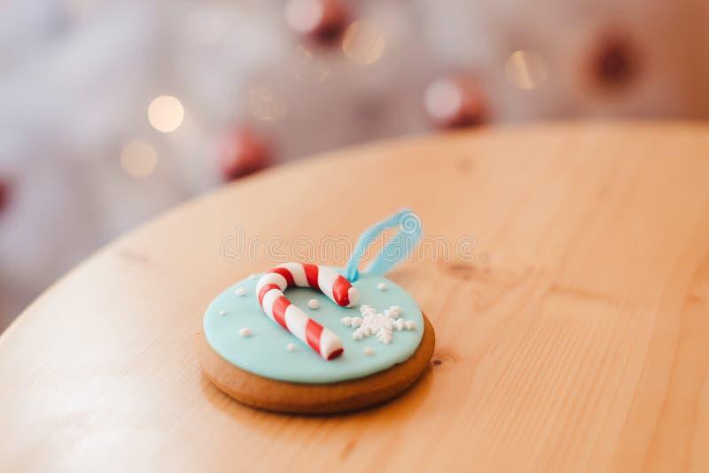 Gingerkaka på bordet nära den vita julgranen med gyllene bokeh-ljus royaltyfria foton