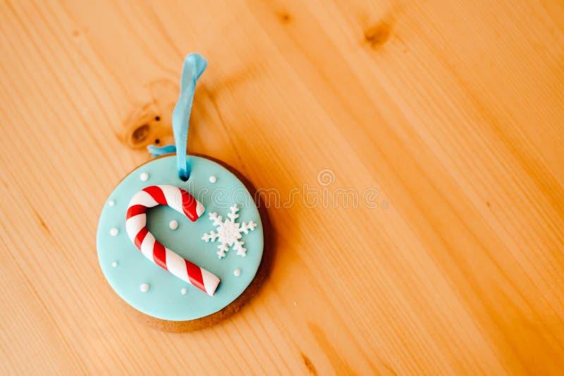 Gingerkaka på bordet nära den vita julgranen med gyllene bokeh-ljus arkivbild