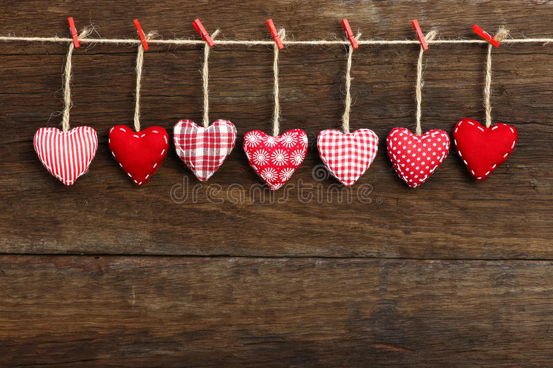 Gingham Love Valentine's hearts hanging on wooden texture backgr. Gingham Love Valentine's hearts natural cord and red clips hanging on rustic driftwood texture stock image