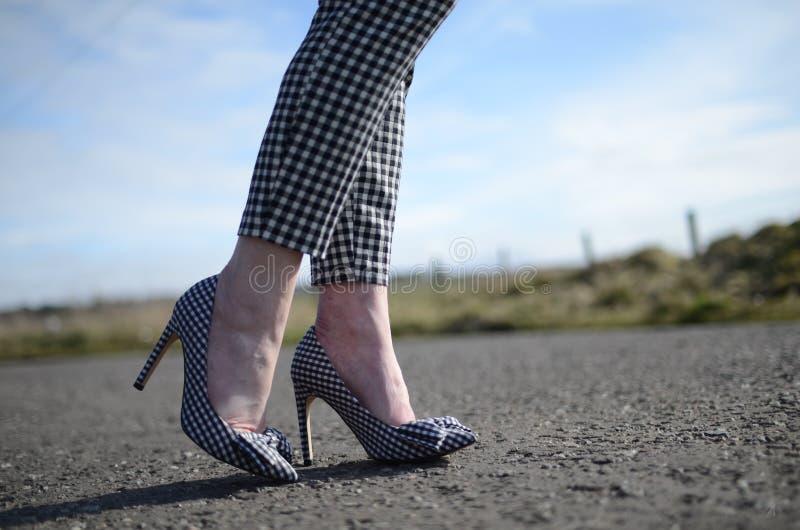 Gingham-Stilettschuh auf dem Fuß der Frau stockfotografie