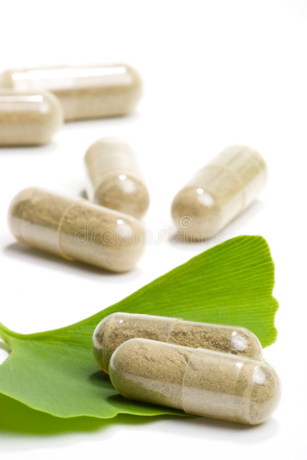 Ginkgo Biloba. Closeup of Ginkgo Biloba extract pills and fresh Ginkgo Biloba leaves best suited for aged people alternative medicine ads stock photography