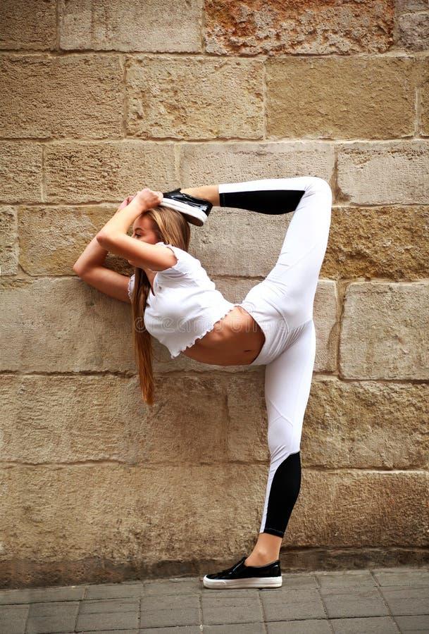 Ginnasta atletica della ragazza che fa allungando esercizio sulla parete di pietra immagini stock