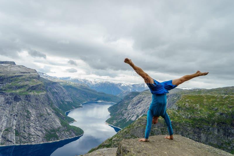 Ginnasta che sta sulle sue mani sul bordo con il fiordo su fondo vicino a Trolltunga norway immagine stock libera da diritti